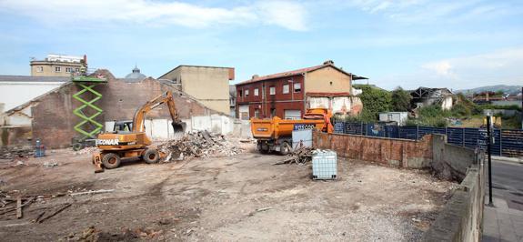 Una excavadora retira escombros en la parcela antes ocupada por una carbonera, entre Coronel Bobes, Almacenes Industriales y Ricardo Montes. / PIÑA